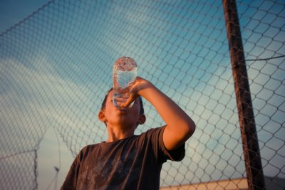 Kid drink water by a fence