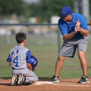 Boy getting batting tips from coach