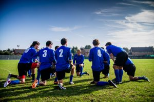 Soccer team in huddle on fielld