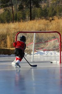 kid playing hockey on ice outside