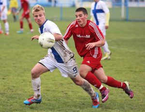 Two opposing team players racing for soccer ball