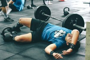 Man laying down next to lifting bar in gym. He is tired due to over training.