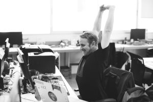 Man Stretching Arms during Break Time at Workplace